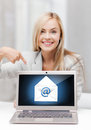 Woman with laptop pointing at email sign Royalty Free Stock Photo
