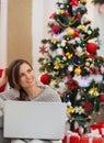 Žena přenosný počítač nejblíže vánoční stromeček