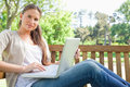 Woman with a laptop sitting on a park bench Royalty Free Stock Photo