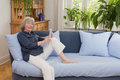 Woman with laptop on sofa cheerful old sitting blue in her living room copy space Royalty Free Stock Images
