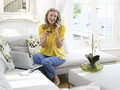 Woman with laptop using credit card and phone happy mature in living room at home Stock Images