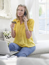 Woman with laptop using credit card and phone mature in living room at home Stock Photo