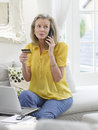Woman with laptop using credit card and phone mature in living room at home Royalty Free Stock Photography
