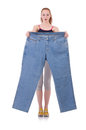Woman with large jeans in dieting concept Royalty Free Stock Photography