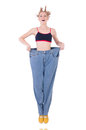 Woman with large jeans in dieting concept Stock Image