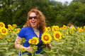 Woman laughing in sunflower field with wavy red hair and sunglasses laughs while standing a of bright yellow sunflowers at mckee Royalty Free Stock Photography