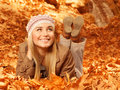 Woman lay down on autumnal foliage Royalty Free Stock Image