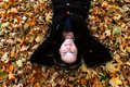 Woman laying in autumn leaves Stock Images