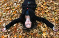 Woman laying in autumn leaves Stock Photography