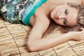 Woman laying on bamboo mat Stock Photos
