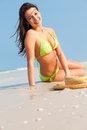 Woman laying on beach latin sitting her side in sand near the surf florida in green bikini vertical Royalty Free Stock Images