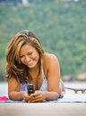 Woman laying on pier text messaging Stock Photos