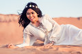 Woman laying in sand of arabian desert Royalty Free Stock Image