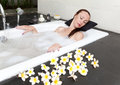 Woman lays in soapsuds in bathing full water Stock Photography