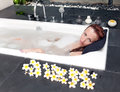 Woman lays in soapsuds in bathing full water Royalty Free Stock Image