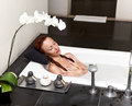 Woman lays in soapsuds in bathing full water Royalty Free Stock Photography