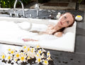 Woman lays in soapsuds in bathing full water Royalty Free Stock Images