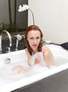 Woman lays in soapsuds in bathing full water portrait in a sunny day Stock Image