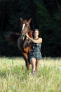 Woman leading horse on halter through the woods equestrienne lead with a rein Stock Images