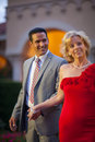 Woman leading man by the hand happy blonde caucasian women in fancy red dress handsome smiling hispanic men in suit and tie Stock Photography