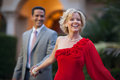Woman leading man by the hand happy blonde caucasian women in fancy red dress handsome smiling hispanic men in suit and tie Stock Photos