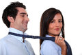 Woman leading a man men by his tie Stock Image