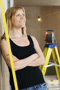 Woman leaning against wall with ladder behind thoughtful smiling young in background Royalty Free Stock Photography