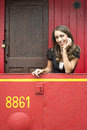 Woman leaning on railing in red train caboose car portrait of beautiful young Stock Images