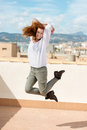 Woman leaping on a flat roof beautiful agile young high in the air with her long red hair streaming out in the wind Stock Images