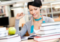 Woman learns sitting at the desk with green apple surrounded with piles of books reads table library training process Stock Photo