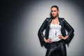 Woman in leather clothes with one hand behind her neck Royalty Free Stock Photo