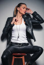 Woman in leather clothes posing while sitting on a stool Royalty Free Stock Photo