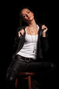 Woman in leather clothes is pulling her collar and sits Royalty Free Stock Photo