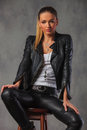 Woman in leather jacket posing seated on stool in studio Royalty Free Stock Photo
