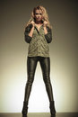 Woman in leather pants posing by holding her collar fashion blonde Royalty Free Stock Photography