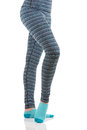 Woman legs in colourful pants and blue socks from the side view standing on one leg with other leg raised Royalty Free Stock Photo