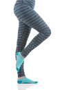Woman legs in colourful striped thermal pants and blue socks from the side view standing on one leg with other led raised Royalty Free Stock Photo