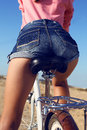 Woman legs in jeans shorts sitting on bicycle Royalty Free Stock Photo