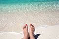 Woman legs lying on sandy beach tropical Stock Image