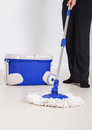 Woman legs with mop and bucket cleaning floor Royalty Free Stock Photo