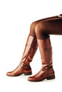 Woman legs wearing brown leather high boots upside down