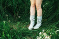 Woman legs in white boots  on green grass. Female feet in shoes Royalty Free Stock Photo