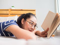 Woman lie on bed and read book.