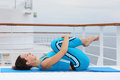 Woman lies on cruise liner deck and does exercise Royalty Free Stock Photography