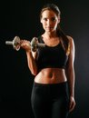 Woman lifting a dumbbell over dark background Royalty Free Stock Photo