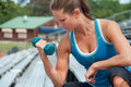 Woman Lifting Weights on Bleachers at Outdoor Track Royalty Free Stock Image