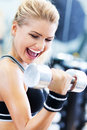 Woman lifting weights in gym exercising with dumbbells Stock Photography
