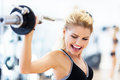 Woman lifting weights in gym exercising with dumbbells Royalty Free Stock Image
