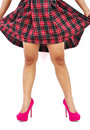 Woman lifts up plaid skirt to show her legs with pink high heel shoes Stock Images