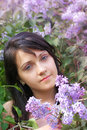 Woman and lilac flowers spring portrait of a beautiful young girl with vertical natural light close up Stock Photo